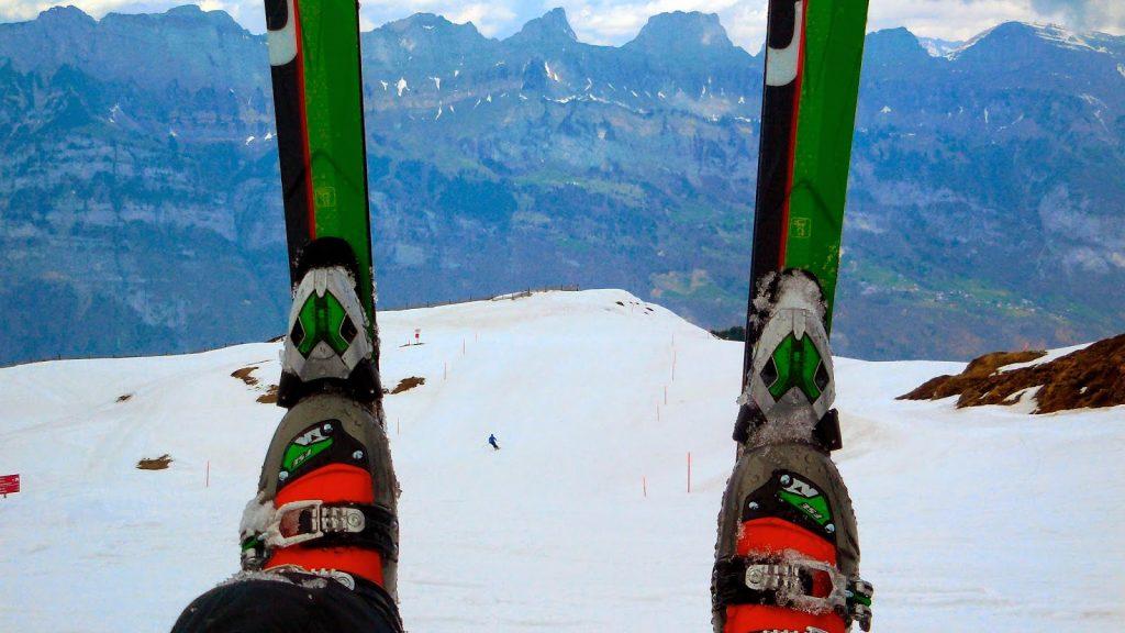 Skifahren im Frühling, weisse Piste und grüne Berge. Im Vordergrund: Skis mit Skischuhen.