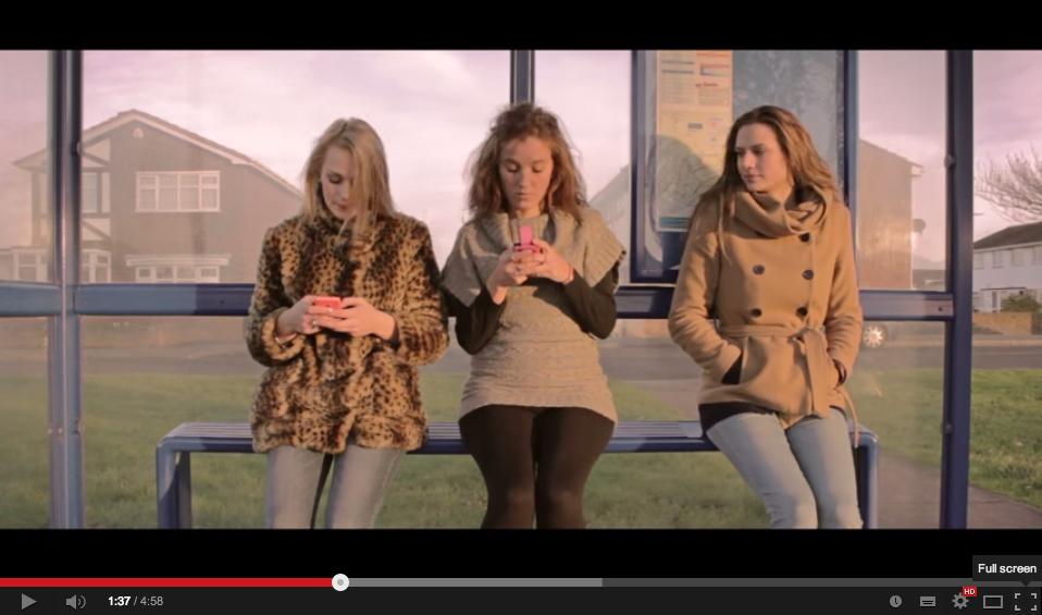 Drei junge Damen warten auf den Bus. Zwei schauen auf ihre Smartphones, eine dritte fühlt sich alleine.